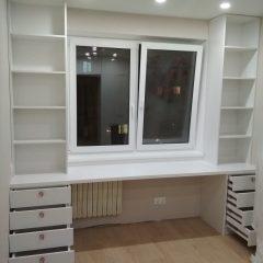 Белый стол под окном со стеллажами и тумбами (1)