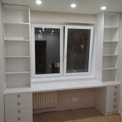 Белый стол под окном со стеллажами и тумбами (2)